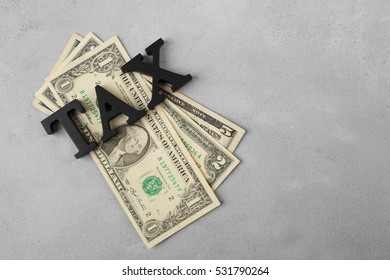 Tax concept with dollar banknotes on grey background, top view