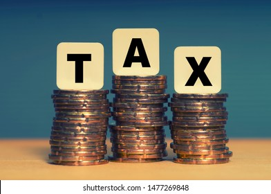 Tax Concept with tax word on stacked gold coins