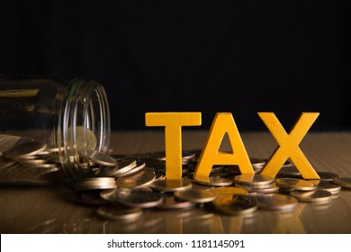 Tax Concept.Word tax put on coins and glass bottles with coins inside on black background.