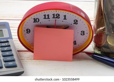 TAX DAY CONCEPT; Clock,red note,calculator and coins in the mason jar over wooden background.