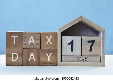 Tax Day concept with wooden calendar 17 May and cube