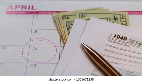 Tax Day , dollars and form 1040 income tax form showing tax day for April Calendar with words