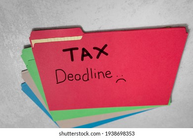 Tax Deadline with sad face written on red file folder accounting cpa background