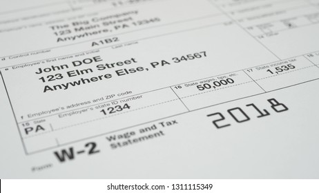 Tax document for the IRS W-2 Tax form on wooden table in office or at home