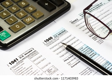 Tax Form 1040, 1041, 1040EZ and pen on a background of a calculator and glasses, close-up