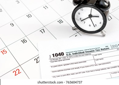 Tax form 1040 with clock on the calendar. Close up. Business concept.