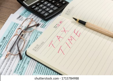 Tax form 1040 with notepad and text tax time, pen and calculator. Tax concept
