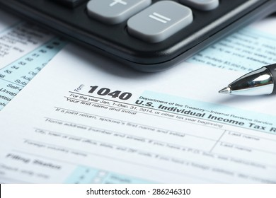 Tax form business financial concept with a pen and a calculator aside.