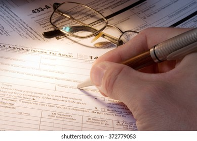 Tax form business financial concept - hand filling in individual return tax form