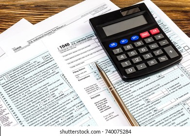 Tax form with calculator and pen on the table.