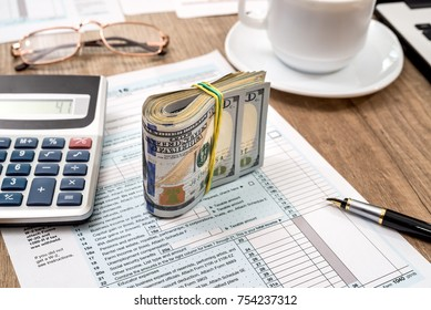 tax form, laptop, coffee and dollar on desk