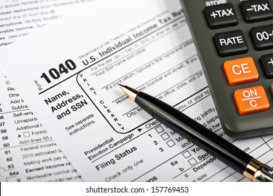 A Tax Form, Pen and Calculator.