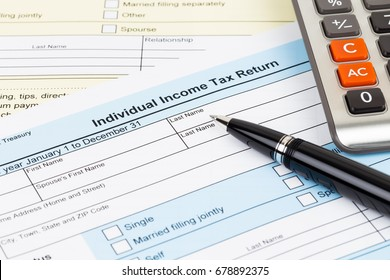 Tax form with pen and calculator; document are mock-up