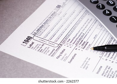 Tax form with pen and calculator, Shallow DOF with focus on 1040