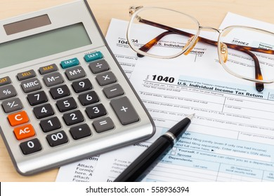 Tax form with pen, glasses, and calculator