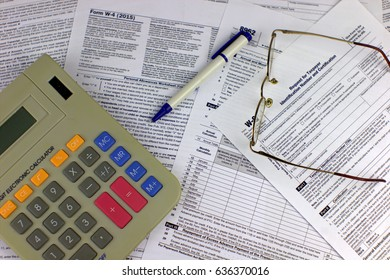 Tax forms with calculator and glasses.