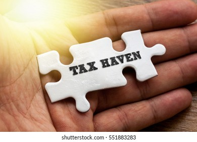 TAX HAVEN written on White color of jigsaw puzzle with hand,conceptual