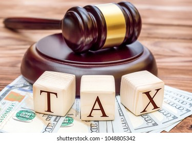 """Tax law concept. Word """" TAX """" with gavel and money on the table."""
