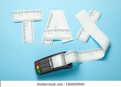 Tax from paper bill and POS terminal for payment on blue background.