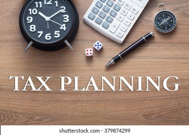 Tax Planning words written on wooden table with clock,dice,calculator pen and compass