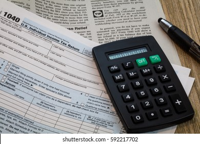 Tax preparation form 1040 detail and instruction booklet with calculator and pen on wood board