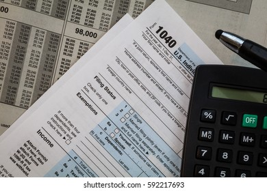 Tax preparation form US 1040 and tax tables with pen and calculator, generic (no year specified)