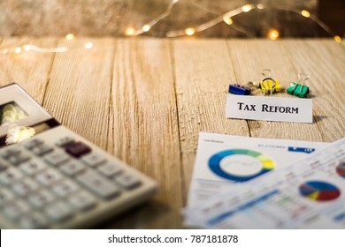 Tax Reform concept with charts and graphs and calculator on wooden board
