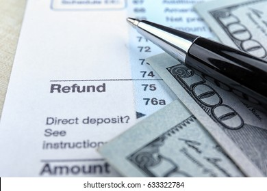 Tax refund document, pen and dollars on table