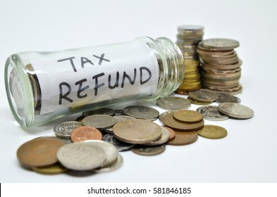 Tax refund lable in a glass jar with coins spilling out isolated on white background