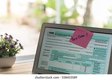 tax return concept. tax time post-it on alarm clock and Individual income tax return form online.