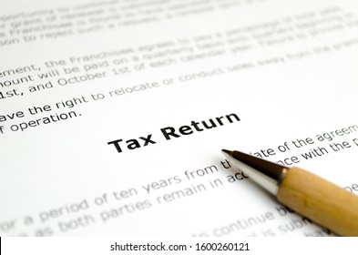 Tax return document with wooden pen