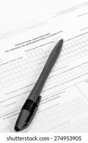 tax return form and ballpoint pen