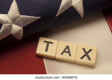 Tax scrabble letters on American flag. Concept of government tax policies.