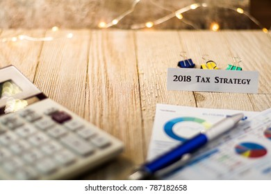 Tax Strategy for 2018 motivational concept with charts and graphs and calculator on wooden board