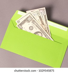 Tax symbol. Some money in green envelope with money on the grey background.
