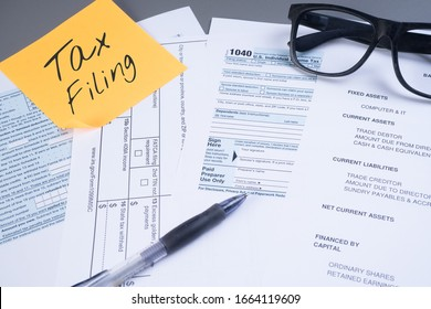 Tax or taxation concept. The tax form is for US citizens and internationals staying in the USA to file their tax return with a yellow note written Tax Filing.