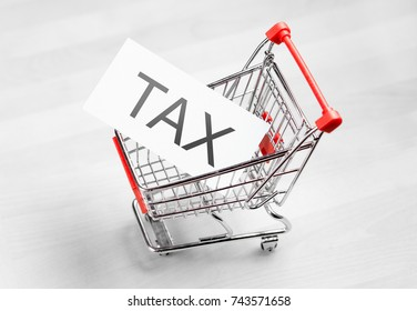 Tax, taxation and VAT concept. Shopping cart with a card or paper sign.