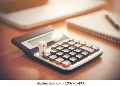 tax text on dice with blurred calculator on wooden table. abstra