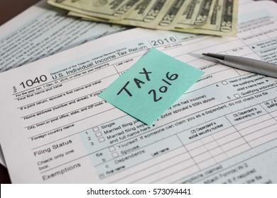 Tax time 2016 written on a written on a bright sticker and  tax form 1040 with pen and twenty dollars banknotes US 1040 tax form with