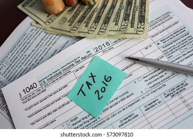 Tax time 2016 written on a written on a bright sticker and  tax form 1040 with pen and twenty dollars banknotes US 1040 tax form with  coin wrappers