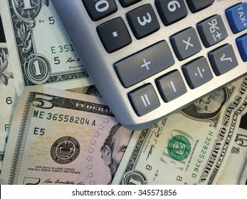 Tax time: calculator sitting on scattered one and five dollar bills.