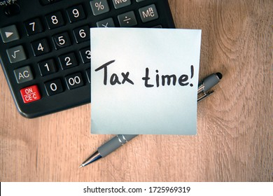 Tax time on blue note sticker with calculator and pen on wooden background