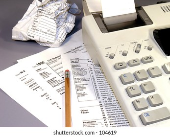 Tax time.  Various IRS forms, calculator, and a pencil.  One of the forms is crumpled.