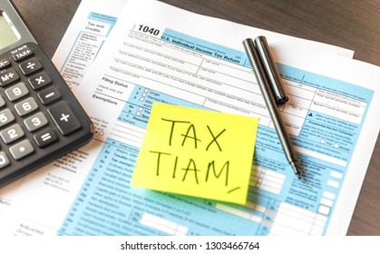 Tax Time written on a blank sticky notes on folder with document about 1040 U.S. Individual Income Tax Reform with pen and calculator on table background.