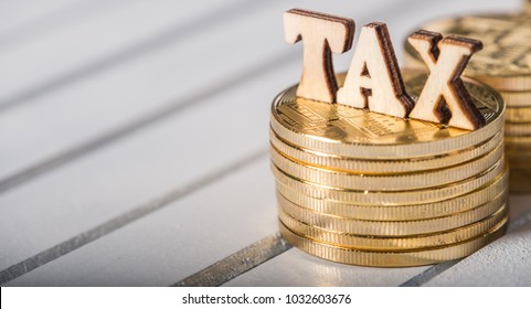 TAX word cryptocurrency golden coin on wooden table top