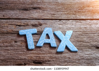 TAX word on wooden background. Financial concept. Selective focus
