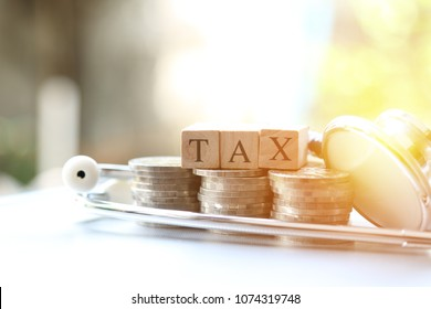 Tax word wooden Blocks and money coin stack