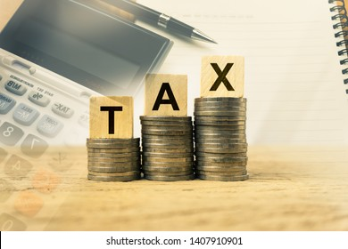Taxation and Annual tax concept. A wooden block with message on stacked coins on wood table exposure with calculator, notebook and black pen. Depicts a income planning, annual tax deduction.