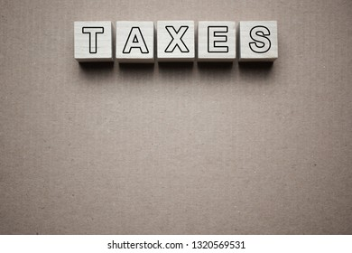 Taxes text written on wooden blocks isolated on piece of grey paper