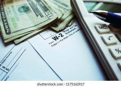 Taxes With W-2 Form, Calculator & Twenty Dollar Bills